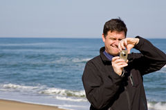 Man using compact camera. Handsome man standing on beach concentrating while using a compact camera Stock Photos