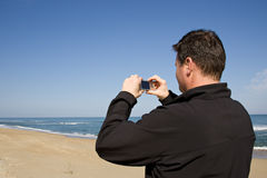 Man using compact camera. Handsome man standing on an empty beach using a compact camera Royalty Free Stock Images