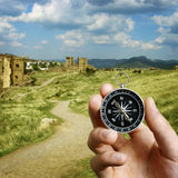 Man using a compass while sightseeing abroad. Conceptual image of the hand of a man using a compass to navigate and find the direction while sightseeing abroad Stock Photo