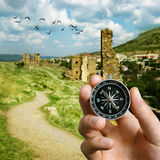Man using a compass while sightseeing abroad. Conceptual image of the hand of a man using a compass to navigate and find the direction while sightseeing abroad Stock Photos