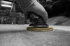 Man using compressed air orbital sander. With selective color stock images