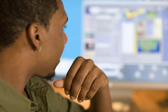 Man using computer. African American young adult looking at computer screen Royalty Free Stock Photos