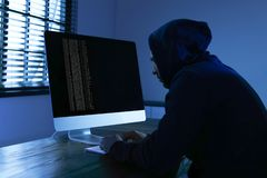 Man using computer in room. Criminal offence. Man using computer in dark room. Criminal offence stock photos