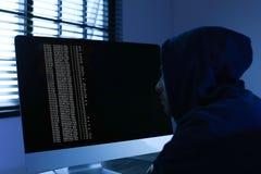 Man using computer. Criminal offence. Man using computer in dark room. Criminal offence stock image