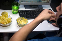 Man using a computer and eating fastfood. Concept of sedentary lifestyle and unhealthy eating habits stock photos