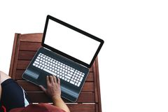 A man using computer lap top on wooden table, white empty computer screen, isolated on white background. Clipping path included Stock Image