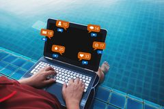 A man using computer laptop at poolside in summer holiday, with social media, social network notification icons. A man using computer laptop at poolside in Royalty Free Stock Image