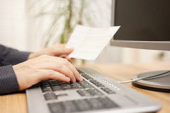Man is using computer  for on line payment. Royalty Free Stock Photo