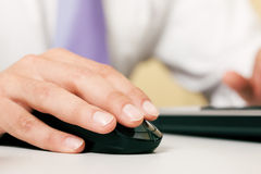 Man using computer mouse. Man (only hand to be seen) using a wireless mouse to operate a computer Royalty Free Stock Photos