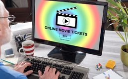 Online movie tickets buying concept on a computer. Man using a computer with online movie tickets buying concept on the screen Royalty Free Stock Images