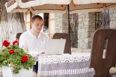 Man using a computer on an outdoor table Stock Image