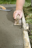 Man using concrete edging tool on wet cement slab. A close up of a man using a concrete edging tool on wet cement slab with timber form work Stock Image