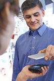 Man Using Contactless Payment App On Mobile Phone In Store. Man Uses Contactless Payment App On Mobile Phone In Store Stock Images