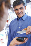 Man Using Contactless Payment App On Mobile Phone In Store. Man Uses Contactless Payment App On Mobile Phone In Store Stock Image