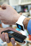 Man Using Contactless Payment App On Smart Watch In Store. Man Uses Contactless Payment App On Smart Watch In Store Stock Image