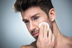Man using cotton pad on face. Handsome man over grey background royalty free stock image