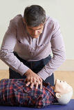 Man Using CPR Technique On Dummy In First Aid Class Royalty Free Stock Photography