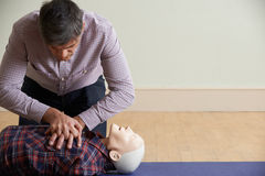 Man Using CPR Technique On Dummy In First Aid Class Stock Photos