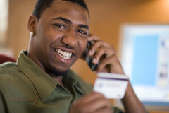Man using credit card and cell phone. Smiling African American man shopping with credit card and cell phone