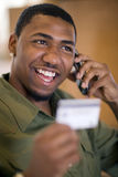 Man using credit card and cell phone. Smiling African American man shopping with credit card and cell phone Royalty Free Stock Image