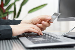 Man is using credit card and computer for  on line payment. Royalty Free Stock Photos