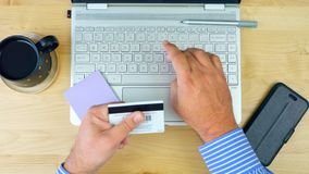 Man using credit card for online shopping with modern laptop, overhead. royalty free stock images