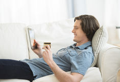 Man Using Credit Card To Shop Online On Digital Tablet Stock Photos
