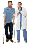 Man using crutches, next to a friendly physician. Happy young men standing while using forearm crutches, next to a friendly female professional physician wearing Stock Photo