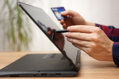 Man is using debit or credit card to pay online on portable touc Royalty Free Stock Photo