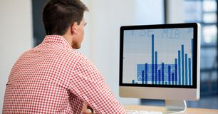 Man using desktop computer displaying a graph chart on screen. At office Stock Photo