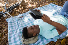 Man using digital while lying on a picnic blanket Stock Photo