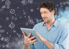 Man using digital tablet against connecting icons. Digital composite image of man using digital tablet against connecting icons stock image
