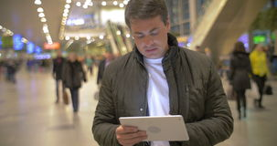 Man using digital tablet in airport hall. Young man in black jacket browsing the internet on tablet computer in crowded airport hall stock footage