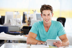 Man Using Digital Tablet In Busy Creative Office Royalty Free Stock Photo