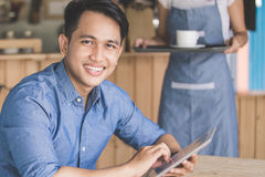 Man using digital tablet in cafe Stock Photography