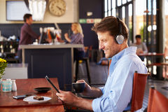 Man using digital tablet in a coffee shop Stock Photo