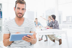Man using digital tablet with colleagues in background Royalty Free Stock Photos