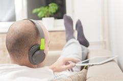 Man using digital tablet computer  at home wearing headphones Royalty Free Stock Photos