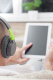 Man using digital tablet computer  at home wearing headphones Royalty Free Stock Photo