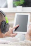 Man using digital tablet computer  at home wearing headphones Royalty Free Stock Photo