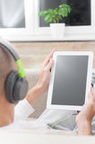 Man using digital tablet computer  at home wearing headphones Stock Photography