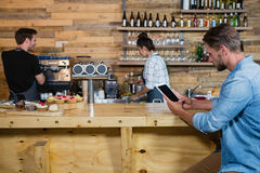 Man using digital tablet at counter. In cafe Royalty Free Stock Photo