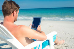 Man using digital tablet on deck chair at the beach Stock Images