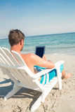 Man using digital tablet on deck chair at the beach Royalty Free Stock Images