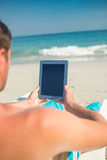 Man using digital tablet on deck chair at the beach Royalty Free Stock Photo