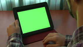 Man using digital tablet with a green screen. To add your own custom content (and alpha matte stock video footage