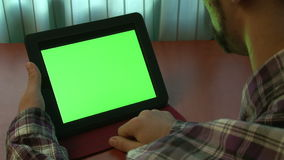 Man using digital tablet with a green screen stock footage