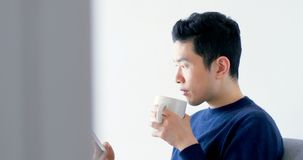 Man using digital tablet while having cup of coffee 4k. Man using digital tablet while having cup of coffee at home 4k stock video