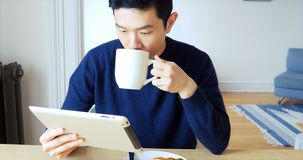 Man using digital tablet while having cup of coffee 4k. Man using digital tablet while having cup of coffee at home 4k stock footage