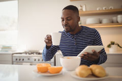 Man using a digital tablet while having cup of coffee in kitchen Stock Image